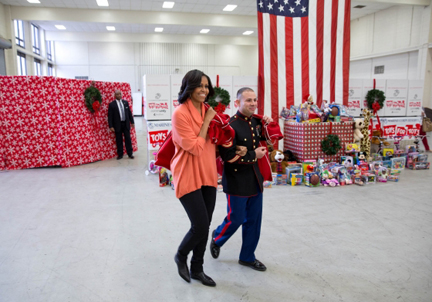 First Lady Michelle Obama is escorted by SSgt Joel Vazquez as she arrives with a sack full of toys at the Toys for Tots Distribution Center at Joint Base Anacostia-Bolling in Washington, D.C., Dec. 11, 2012. (Official White House Photo by Lawrence Jackson)
