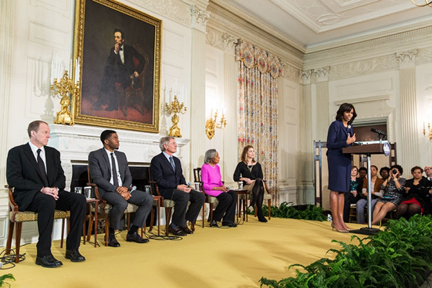 "First Lady Michelle Obama delivers remarks during the ""42"" film workshop in the State Dining Room of the White House, April 2, 2013. Workshop participants included, from left, Brian Helgeland, Chad Boseman, Harrison Ford, Rachel Robinson, and moderator Paulette Aniskoff. (Official White House Photo by Chuck Kennedy)"
