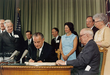 President Lyndon B. Johnson signs Medicare into law. President Harry Truman seated at right.